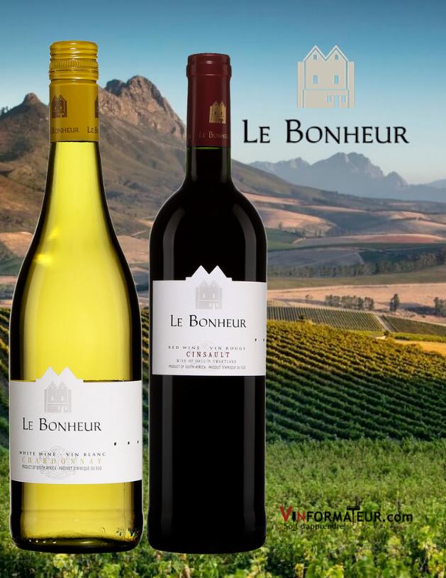 Bouteilles de Le Bonheur Chardonnay 2020 et Cinsault 2019 avec vignoble en arrière-plan